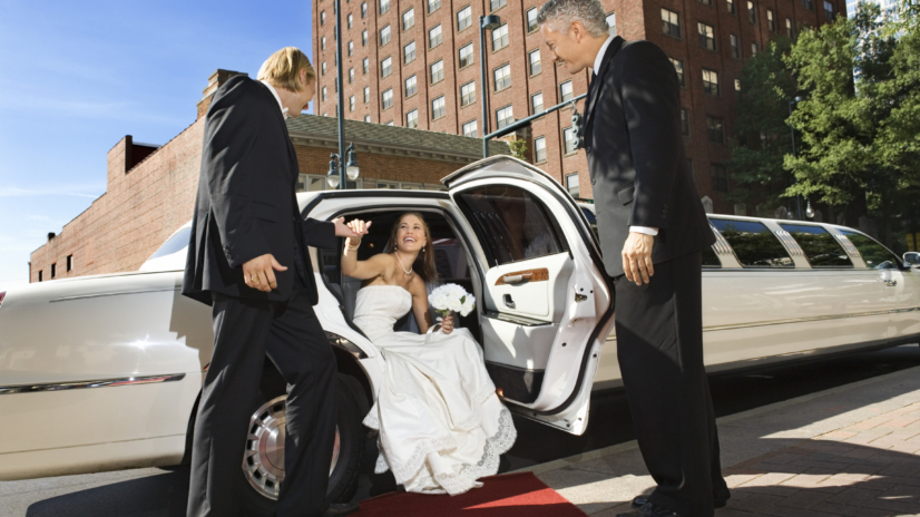 Bride and groom getting out of limo