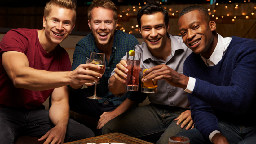 Portrait Of Male Friends Enjoying Night Out At Rooftop Bar